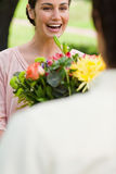 Woman laughing as she is being presented with flowers Stock Images