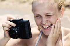 Woman laughing as she views a photo Stock Images