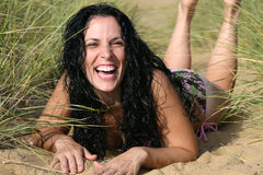 Woman laughing on beach. Woman wearing bikini laying down at beach laughing Stock Photography