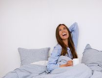Woman laughing in bed with cup of coffee Royalty Free Stock Image