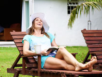 Woman laughing with book in backyard Stock Image
