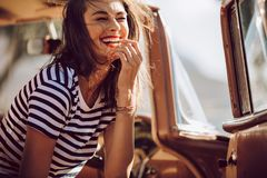 Woman laughing in a car. Beautiful woman sitting in a car and laughing. Woman having fun outdoors on the road trip Stock Photos