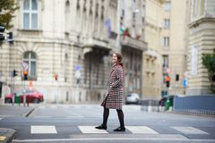 Woman laughing crosses the street at pedestrian crossing in Budapest. Stock Image