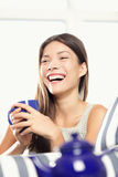 Woman laughing drinking tea Stock Photo