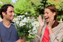 Woman laughing excitedly as she is presented with flowers by her Royalty Free Stock Photography