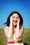 Woman laughing in field. A beautiful young woman laughing in a field with a blue sky stock photo