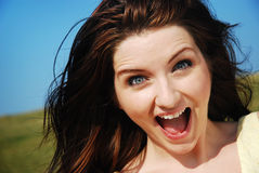 Woman laughing in field. A young woman laughing in a field with a blue sky stock images