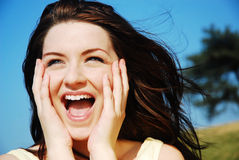 Woman laughing in field. A beautiful young woman laughing in a field with a blue sky stock photography