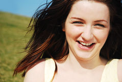 Woman laughing in field. A beautiful young woman laughing in a field with a blue sky. Genuine laughter stock photography