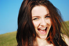 Woman laughing in field. A young woman laughing in a field with a blue sky stock photography