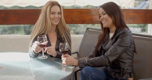 Woman laughing with friend over wine. Pair of female friends in leather jackets having fun talking and drinking wine together outside stock footage