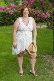 Woman laughing with hat. Forty something woman under a cherry tree holding a straw hat Stock Photography