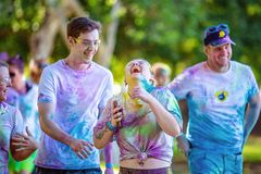 Woman Laughing Heartily In Color Frenzy Fun Run. MACKAY, QUEENSLAND, AUSTRALIA - JUNE 2019: Unidentified young woman laughing out loud with friends in Color stock photography