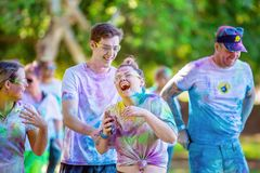 Woman Laughing Heartily In Color Frenzy Fun Run. MACKAY, QUEENSLAND, AUSTRALIA - JUNE 2019: Unidentified young woman laughing out loud with friends in Color stock photos
