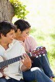 Woman laughing with her friend who is playing the guitar Stock Photography