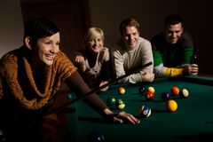 Woman laughing at snooker table. Woman laughing holding cue at snooker table, friends in background Stock Photos