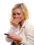 Woman laughing. A woman is laughing while holding her cell phone stock photo