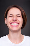 Woman is laughing loudly. Emotional woman is laughing loudly over dark background Royalty Free Stock Photography