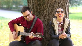 Woman laughing and man playing guitar while sitting on a tree in park stock footage
