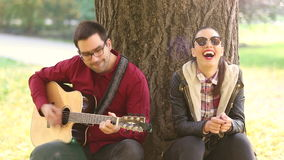 Woman laughing and man playing guitar while sitting on a tree in park stock video footage