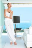 Woman laughing in modern living-room. Woman standing laughing in casual white outfit in a modern glass fronted living room with a view of the ocean Royalty Free Stock Photo