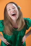 Woman Laughing Out Loud. Beautiful Caucasian woman laughing loud out on an orange background Stock Photos
