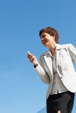 Woman laughing over a message on her mobile Royalty Free Stock Images