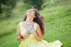 Woman laughing in the park. Reading e-book Royalty Free Stock Photography