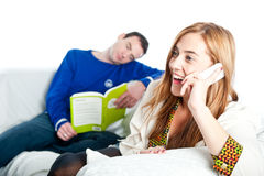 Woman laughing on the phone with boyfriend in the background Stock Photography