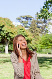 Woman laughing on the phone while looking towards the sun Royalty Free Stock Image