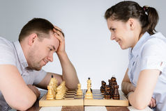 Woman laughing while playing chess against a brooding man Royalty Free Stock Images