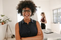 Woman laughing during presentation in office. Portrait of young african businesswoman standing with her arms crossed in meeting room with colleague giving stock image