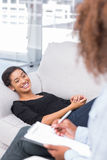 Woman laughing on sofa during therapy session Stock Photography