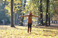 Woman laughing after throwing leafs. Beautiful girl smiling and playing with leafs in park Royalty Free Stock Image