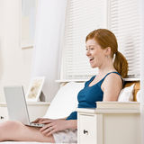 Woman laughing while using laptop in bed Royalty Free Stock Photo