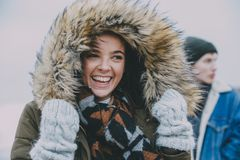 Woman Laughing On A Winter Beach. A women laughing on a winter beach with an out of focus male in the background royalty free stock images