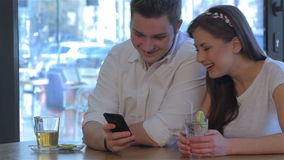 Woman laughs looking at the man`s phone. Pretty caucasian girl laughing after seeing something interesting on the man`s phone. Handsome man showing something stock video