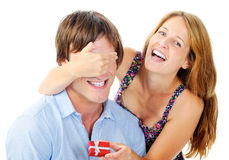 Woman laughs when she surprises her boyfriend. Pretty women is happy to give her boyfriend an anniversary gift Stock Photo