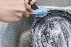 Woman launches a burnt pan with a blue brush in the kitchen sink. Royalty Free Stock Photography