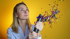 Woman launches confetti on a yellow background slow motion stock video