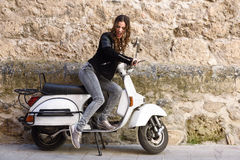 Woman launching a old scooter with pedal Stock Image