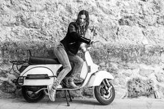 Woman launching a old scooter with pedal Stock Photography