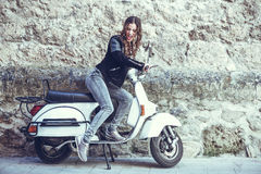 Woman launching a old scooter with pedal Royalty Free Stock Photo