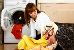 Woman with laundry. A beautiful woman doing laundry in her home (house) selecting different color clothes stock photos