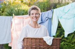 Woman with laundry basket. Cheerful senior woman holding laundry basket in front of the clothesline. Portrait of old woman drying clothes. Senior woman hanging Stock Photo