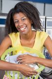Woman With Laundry Basket At Laundromat. Portrait of happy young woman with laundry basket at laundromat stock image