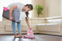 Woman with laundry basket picking clothes from floor in living room Stock Images