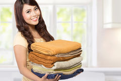 Woman with laundry. Woman doing a housework holding laundry at home Stock Images