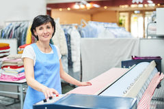 Woman Laundry worker pats the linen on the automatic machine. At the dry cleaners Royalty Free Stock Photos