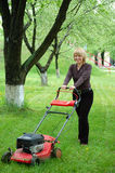 Woman with lawn-mower. Smiling pretty blonde woman moving a lawn-mower Royalty Free Stock Photos